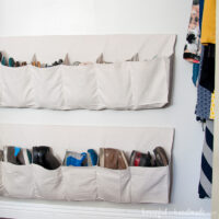 Two hanging shoe storage with rows of pockets sewn from a drop cloth.