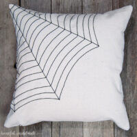 Drop cloth throw pillow with spiderweb design sewn in one of the corners laying on a wood background.