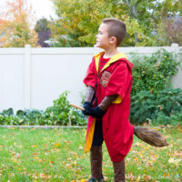 Young boy wearing a DIY Harry Potter Quidditch costume in red for the Gryffindor team and riding a DIY broom.