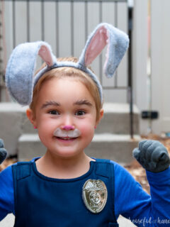 Young girl wearing a DIY Judy Hopps halloween costume with ears and face painted as a bunny.