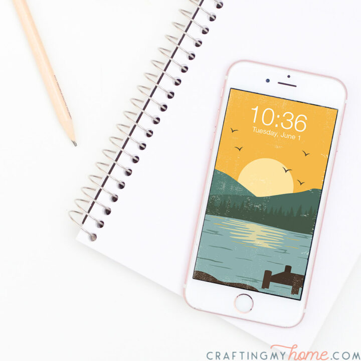 White iPhone with a vintage inspired lake sunset digital wallpaper on the home screen sitting on a sketchpad.