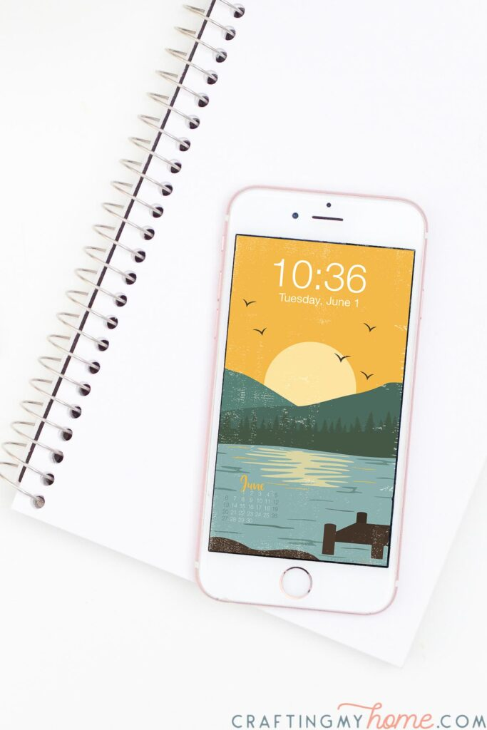 Lake art digital background with yellow sky and setting sun behind teal mountains and a pale lake in the front on a phone screen.