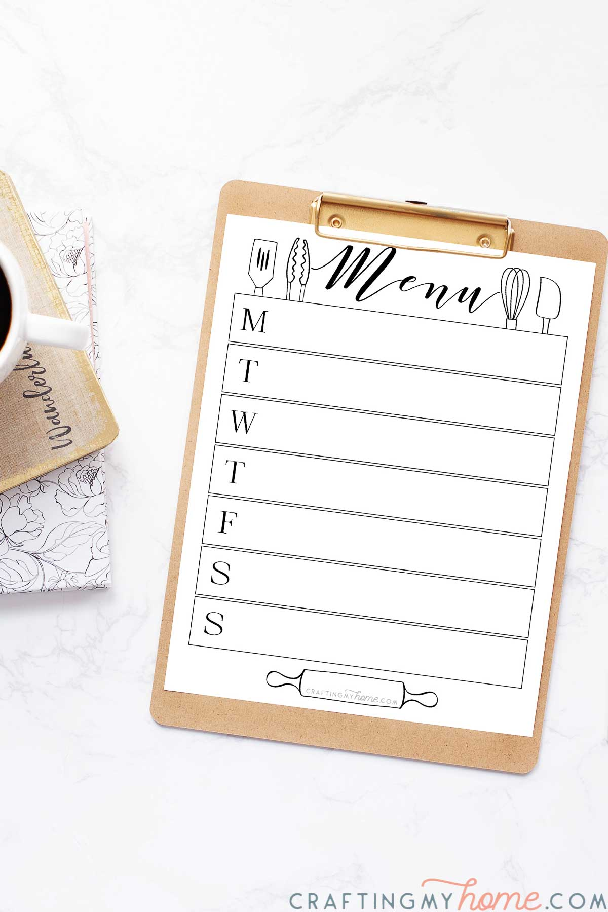 White printable menu board with utensil designs on it clipped to a clipboard next to a planner and cup of coffee.