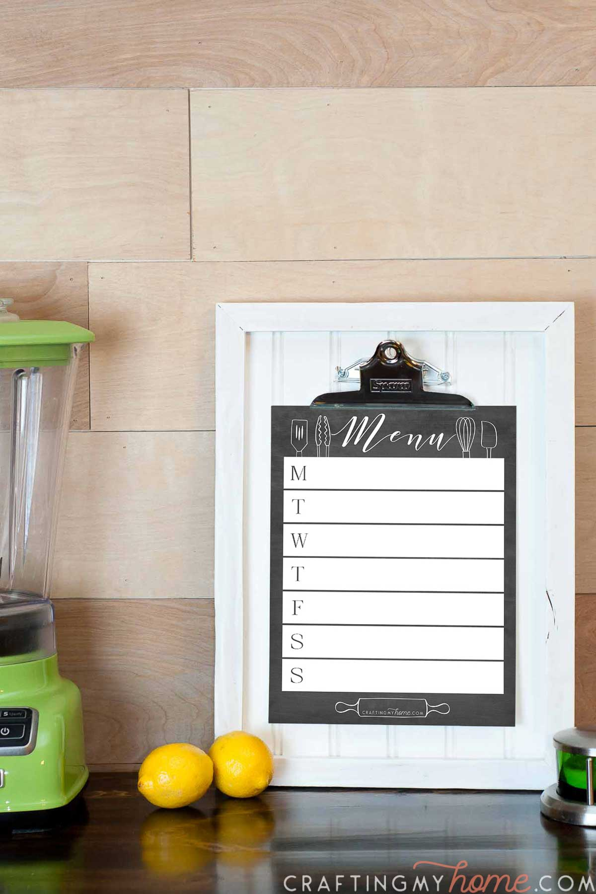 White clipboard picture frame with chalkboard weekly menu planner clipped to it and kitchen stuff around it.