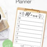 White and black weekly menu planner printed on paper and clipped to a clipboard with text overlay: Printable weekly menu planner.