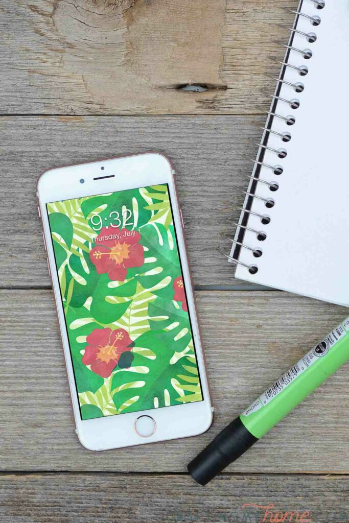 White iPhone with tropical wallpaper on the home screen sitting on a wood desk next to a sketchpad.