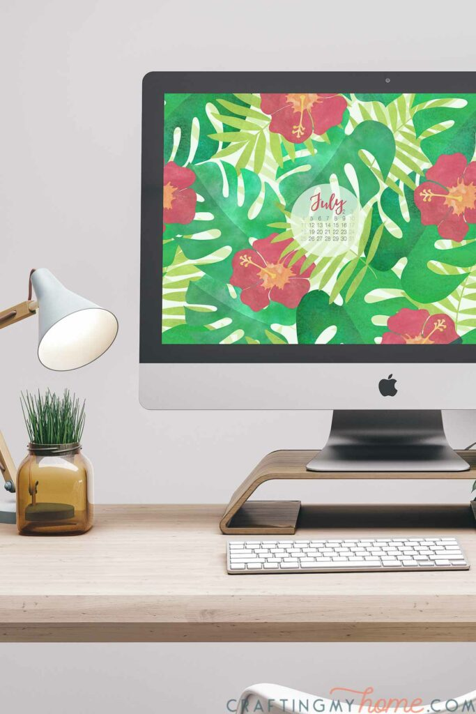 Desktop computer with free digital wallpaper for July on the screen with a July 2021 calendar.