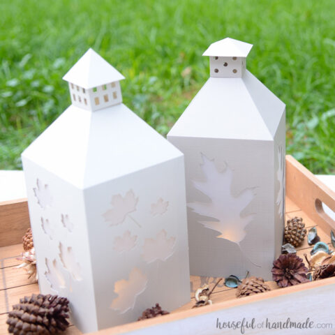 Two fall candle lanterns made out of neutral toned paper sitting in a decorative tray.