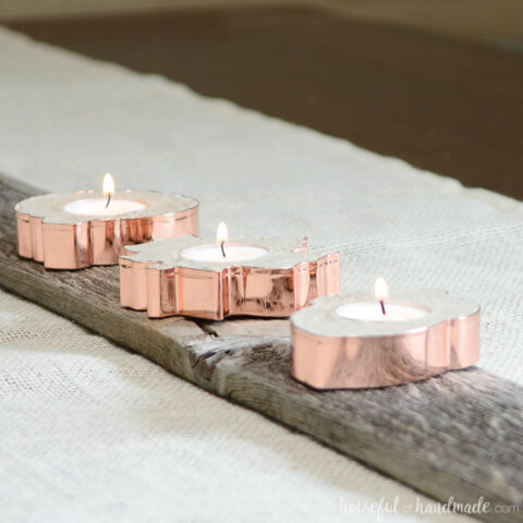 Three copper candle holders in the shapes of fall leaves and acorns on a rustic board.