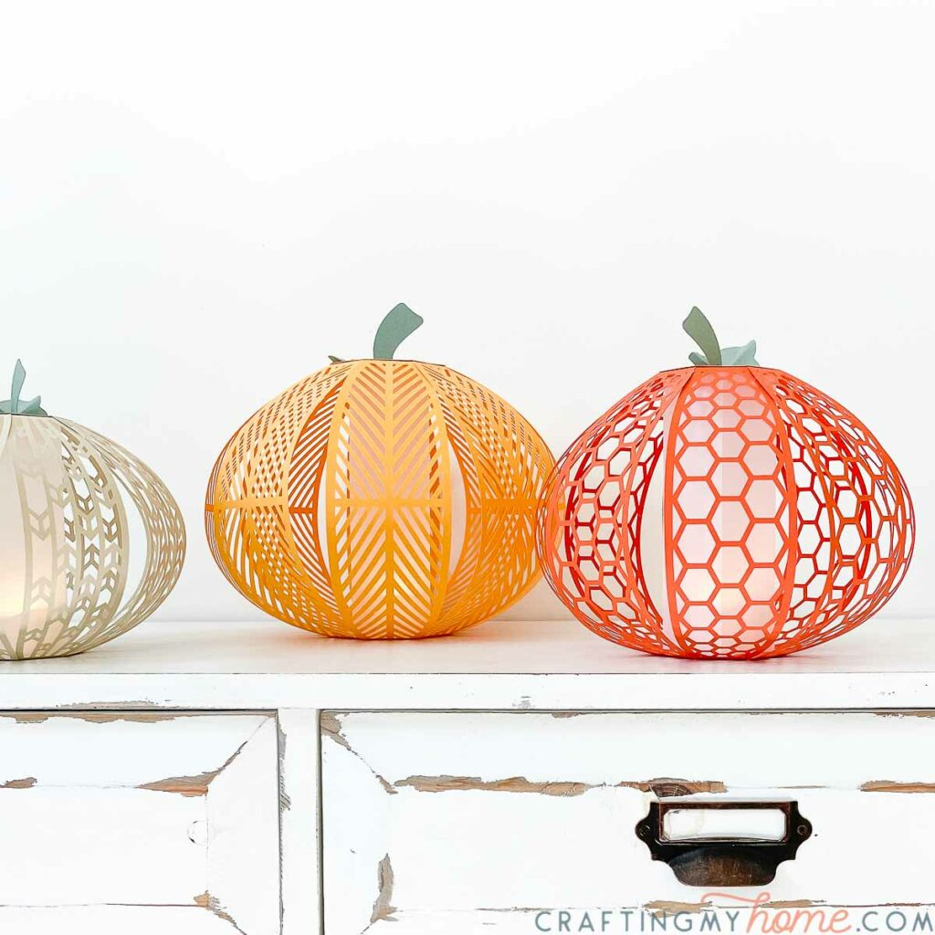 Cream, yellow-orange, and orange paper pumpkin lanterns in 3 different patterns and sizes sitting on a side table.