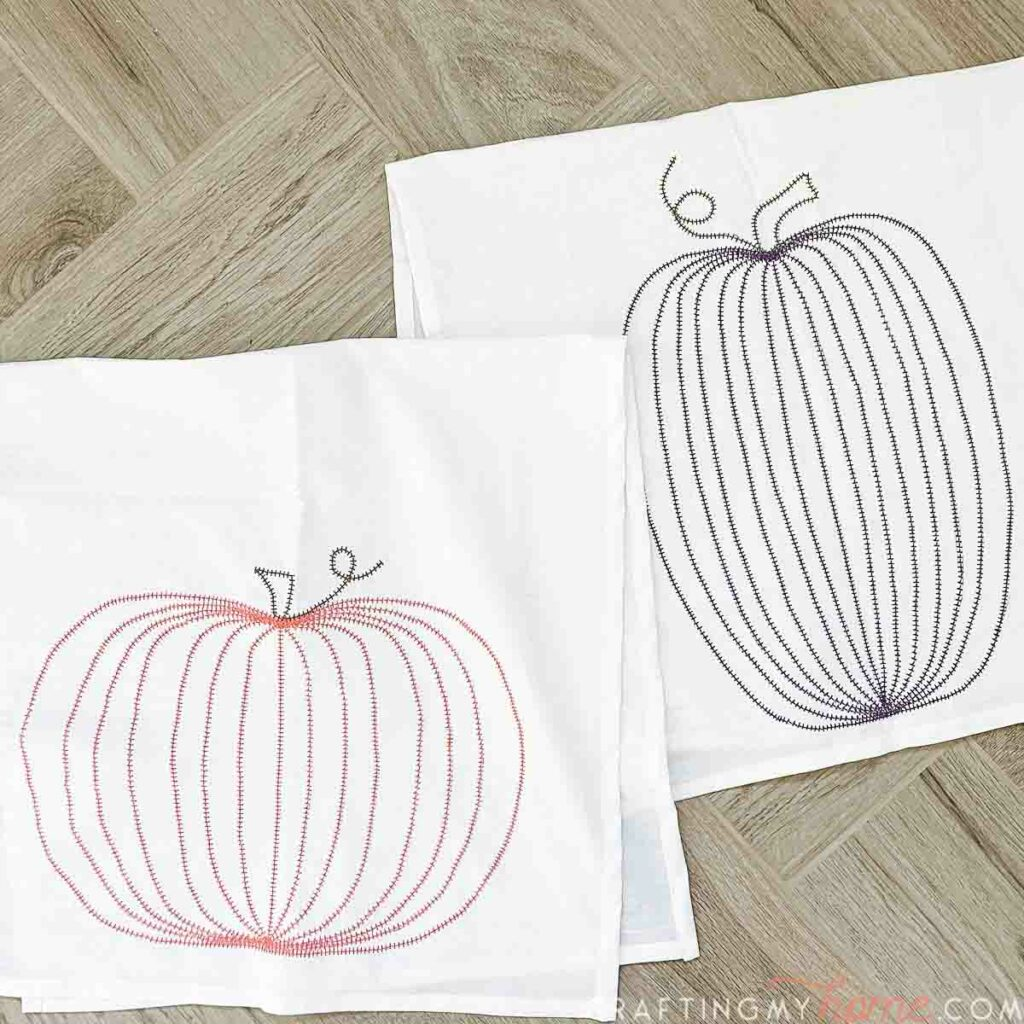 Two DIY pumpkin tea towels with a simple pumpkin design sewn into the fabric laying on a wood background.