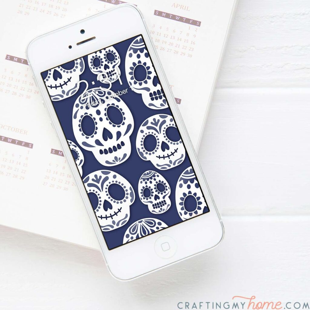 White iPhone with blue and white sugar skull pattern as the digital wallpaper on the home screen.