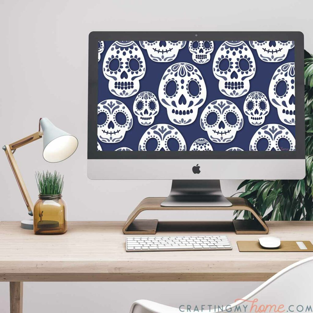 Computer sitting on a desk with the October digital background of sugar skulls on it.