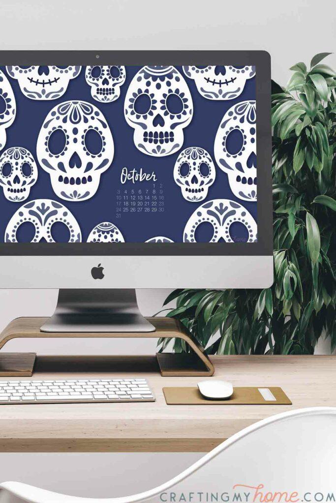 Desktop computer showing the sugar skull free digital wallpaper for October on the screen.