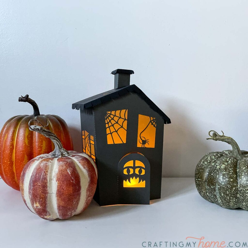 Haunted house halloween lantern made from paper with flameless tea light inside and pumpkins around it.