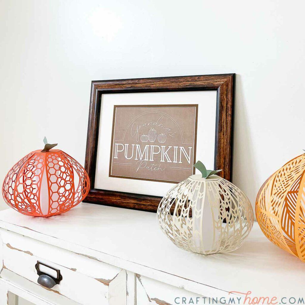 Pumpkin patch printable art in a frame next to paper pumpkin lanterns.