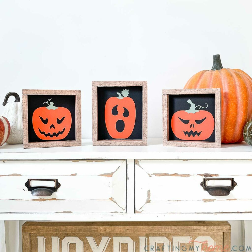 Three simple Halloween signs of jack-o-lanters on a black background with faux wood frames.